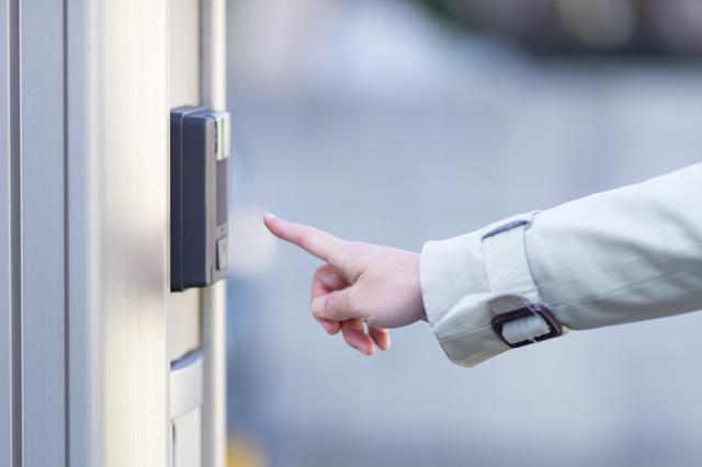 インターホンを押す女性の手