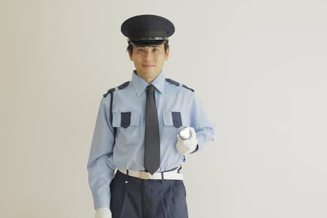 懐中電灯を持つ警備員