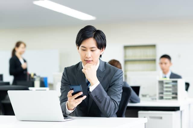 職場でスマホをチェックする男性