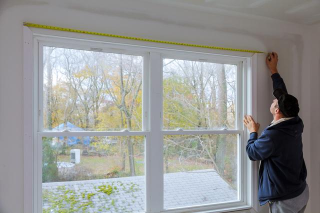 窓のサイズを測る男性