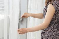 ガラス窓を閉める女性